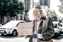 Miserable dirty old man being poor homeless and standing with cardboard. Dirty homeless. Miserable dirty old man being poor homeless and standing with cardboard stock image