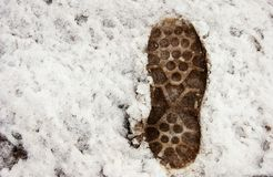 Dirty human footprint on the snow Royalty Free Stock Photo
