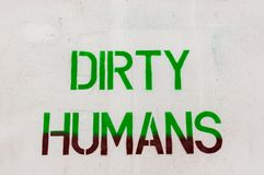 Dirty humans written on white wall Royalty Free Stock Image
