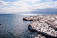 Dirty ice edge and melting floes by water under partly cloudy sk Royalty Free Stock Image