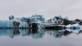 Dirty Icebergs on Jokulsarlon Lake, Southern Iceland. Icebergs with mineral impurities reflected in the calm waters of Jokulsarlon Lake, Southern Iceland Royalty Free Stock Image