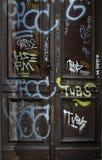 Dirty inscripted den gamla dörren Arkivbild