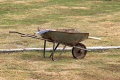 Dirty iron trolley for manual moving of building materials in the city park royalty free stock image