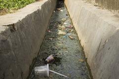 Dirty irrigation ditch Ecological problems. Heap trash Stock Photo