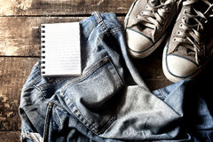 Dirty jeans notepad and sneakers Royalty Free Stock Photos