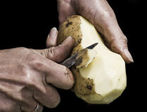Dirty job!. Man's hands peeling potato with serrated knife fading into black background. Shot with macro lens, very detailed image Stock Photo