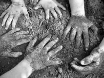 A Dirty Kid is a Happy Kid 2. Three pairs of very dirty hands.  Children playing in the dirt.  Black and White image Stock Images