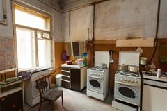 Dirty kitchen with furniture and gas stoves is in the apartment for temporary living existence refugees who were forced to mig. Rate and emigrate from other stock images
