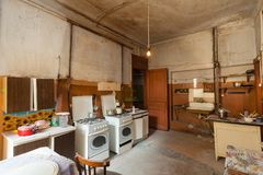 Dirty kitchen with furniture and gas stoves is in the apartment for temporary living existence refugees who were forced to mig. Rate and emigrate from other stock image
