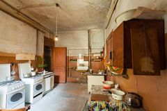 Dirty kitchen with furniture and gas stoves is in the apartment for temporary living existence refugees who were forced to mig. Dirty kitchen with furniture and Royalty Free Stock Photos