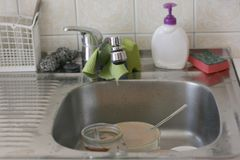 Dirty kitchen sink. With different old cleaning sponges, focus on tip of faucet stock photography