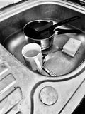 Dirty kitchen things. Mug, cutlery and dirty kitchen in black and white scene. Rubbish concept stock photo