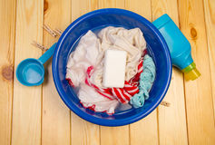 Dirty laundry in blue bowl with soap Royalty Free Stock Photography