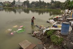 Dirty Laundry: Washerman wash clothes in polluted water royalty free stock photos