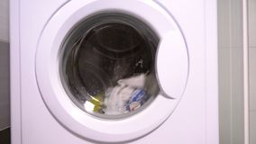 Dirty laundry in an automatic washing machine. Dirty laundry washing in an automatic washing machine in a rotating wash cycle viewed through the door stock video footage