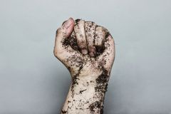 Dirty left fist raising up in front of grey background Stock Photo