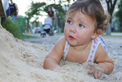 Dirty little girl lying in the sand near the playground. Royalty Free Stock Images