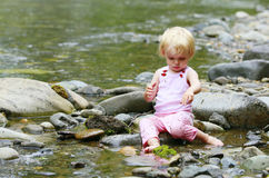 Dirty little girl in a pink suit sitting on the rocks in the river Stock Photo