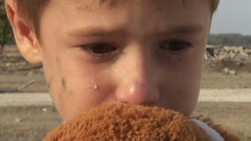 Dirty little orphan boy close-up crying and. Petting a stuffed toy on the background of the ruins of the destroyed houses stock footage