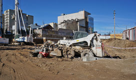Dirty machines on building. VILNIUS, LITHUANIA - APRIL 02, 2016: Ditch on Narbuto street with dirty construction equipment which is rented at Cramo. The company' royalty free stock photos
