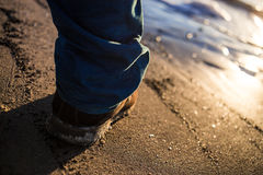 Dirty Male shoes on textured sea sand contrast blue trousers Royalty Free Stock Photo