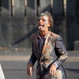 Dirty man as a dog. AURILLAC, FRANCE - AUGUST 22: a very dirty man is sticking out his tongue in the street,  Aurillac International Street Theater Festival Stock Image