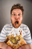 Dirty man chewing hamburger Royalty Free Stock Image