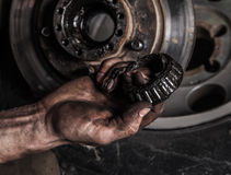Dirty man hand with gear. And car wheel stock photos