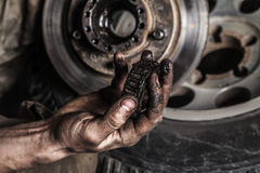Dirty man hand with gear. And car wheel royalty free stock photos