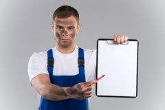 Dirty man holding clipboard and showing blank. Royalty Free Stock Photo