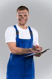 Dirty man writing on clipboard and smiling. Stock Images