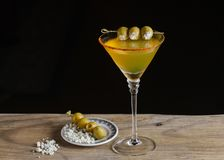 Dirty Martini Cocktail garnished with stuffed olives. Dirty Martini Cocktail on dark background royalty free stock images