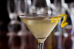 Dirty martini with a lemon twist. Dirty martini chilled and served on a busy bar top with a shallow depth of field and color lights and glasses in the background royalty free stock photos