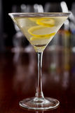 Dirty martini with a lemon twist. Dirty martini chilled and served on a busy bar top with a shallow depth of field and color lights and glasses in the background royalty free stock photography