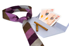 Dirty money. Man's tie lying beside envelope with money inside and few cigarillos lying near Royalty Free Stock Photography