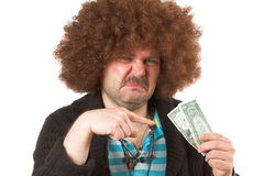 Dirty money. Old hippie looking at the money in his hand with a dirty look on his face Royalty Free Stock Images