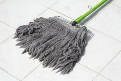 Dirty mop. On white floor tiles Royalty Free Stock Photography