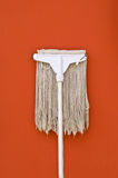 Dirty mop against on brown wall Stock Image