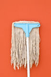 Dirty mop on brown wall Royalty Free Stock Photo