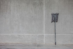 A dirty mop leaned on the cement wall Royalty Free Stock Photos