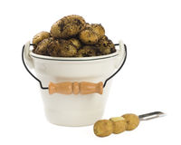 Dirty New Potatoes. Freshly dug organic new potatoes in pail with peeler on white background stock image
