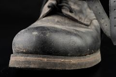 Dirty old black military boots from the mud. Footwear resistant to difficult terrain conditions. Dark background abstract antique army casual closeup clothes royalty free stock photography