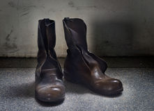 Dirty old brown boots over blue grunge background Royalty Free Stock Image