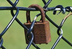 Dirty old corrosive padlock. On wire mesh fence royalty free stock images