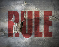 Dirty and old cracked concrete wall with word. RULE on it close up Stock Image