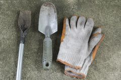 Dirty and old garden shovels and gloves on concrete floor. Top view Stock Image
