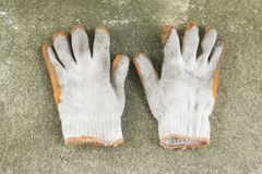 Dirty and old glove on concrete floor. Top view Royalty Free Stock Images