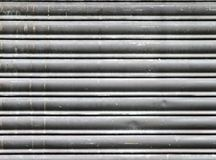 Dirty old grey stained horizontal closed steel rolling security shutters royalty free stock photo
