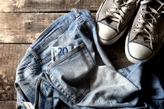 Dirty old jeans twenty euro bill and sneakers Stock Photo