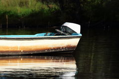 Dirty old motor boat in lake stock photos